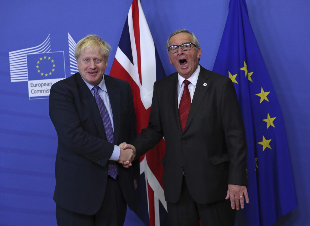 FILE - In this Thursday, Oct. 17, 2019 file photo British Prime Minister Boris Johnson shakes hands with European Commission President Jean-Claude Jun...