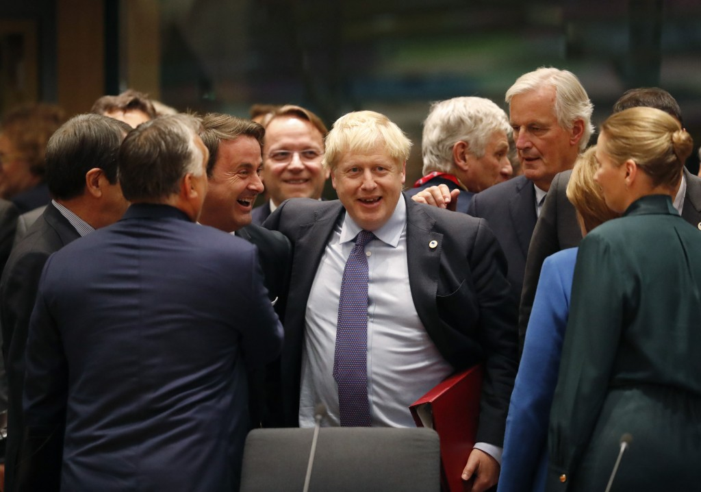 FILE - In this Thursday, Oct. 17, 2019 file photo British Prime Minister Boris Johnson, center, is greeted by Luxembourg's Prime Minister Xavier Bette...