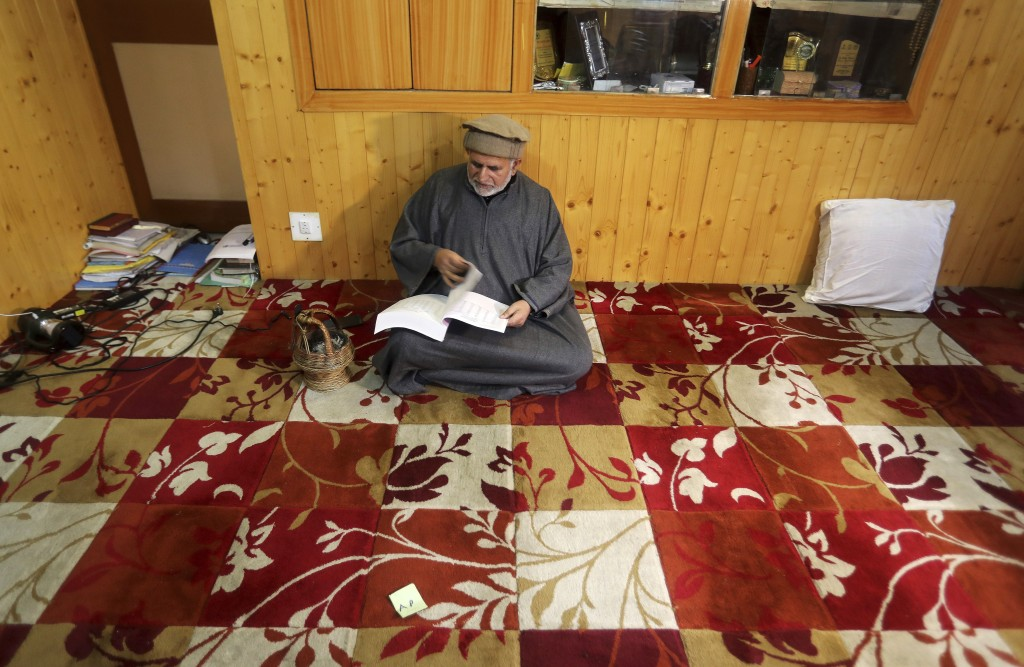 In this Nov. 16, 2019 photo, Sheikh Showkat, a professor of international law and human rights at the central university of Kashmir reads a book insid...
