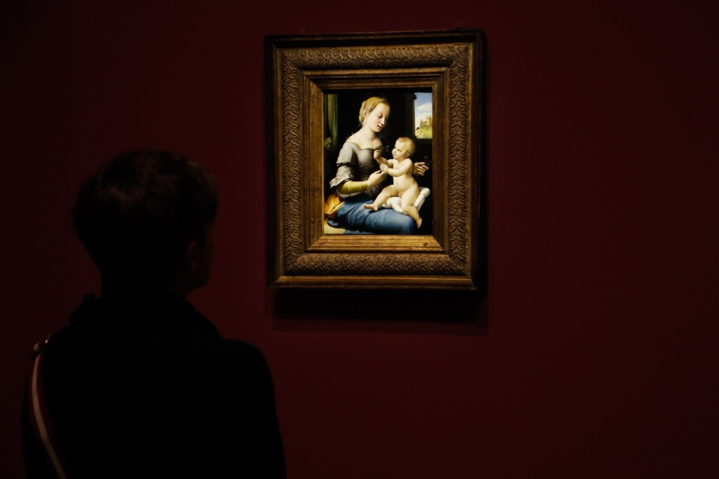 A woman looks at 'Madonna of the Pinks' of Renaissance artist Raphael from London's National Gallery which is on display at an exhibition at the Gemae...