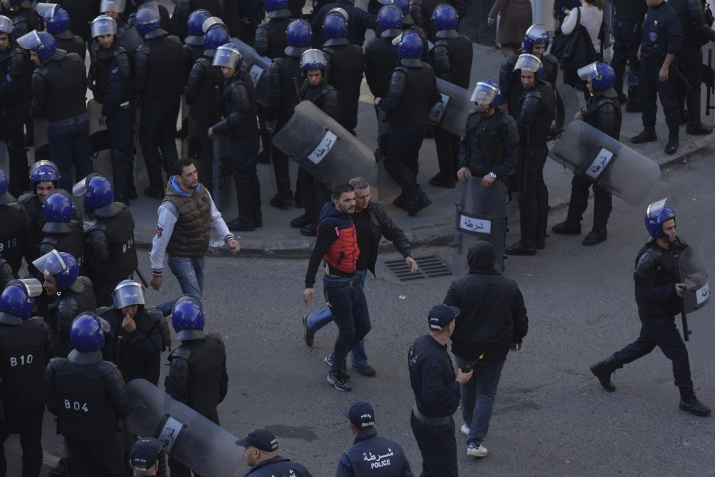 Security forces arrest a man as protesters take to the streets in the capital Algiers to protest against the government and reject the upcoming presid...