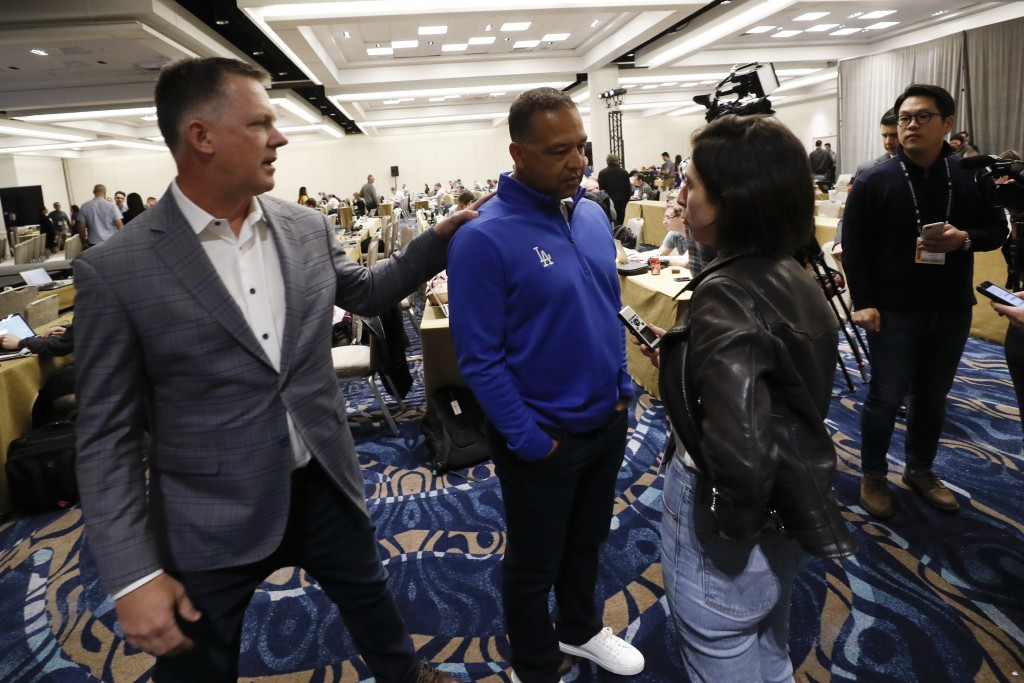 Houston Astros manager A.J. Hinch, left, greets Los Angeles Dodgers manager Dave Roberts, center, during the Major League Baseball winter meetings, Tu...