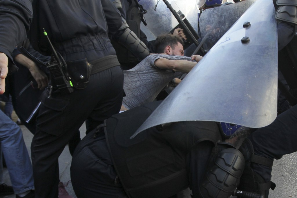 Security forces arrest a man as Algerian demonstrators take to the streets in the capital Algiers to protest against the government and reject the upc...