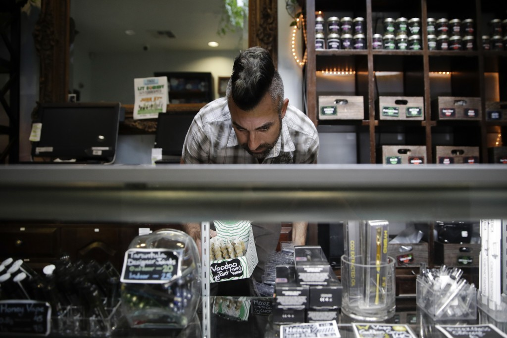 FILE - In this June 27, 2017, file photo, Jerred Kiloh, owner of the licensed medical marijuana dispensary Higher Path, stocks shelves with with canna...