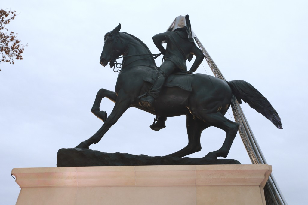 A tarp still covers part of a statue during the unveiling ceremony for a statue titled Rumor's of War by artist Kehinde Wiley at the Virginia Museum o...
