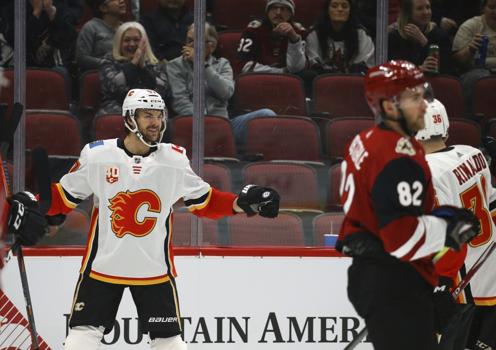 Calgary Flames right wing Michael Frolik, left, celebrates his goal with Flames center Zac Rinaldo (36) as Arizona Coyotes defenseman Jordan Oesterle ...
