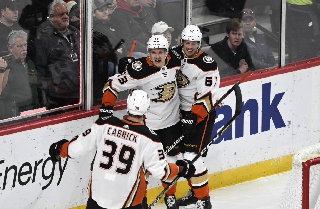 Anaheim Ducks' Rickard Rakell, right, of Sweden, celebrates with teammates Jakob Silfverberg, center, of Sweden and Sam Carrick (39) in the first peri...
