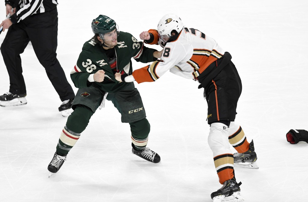 Minnesota Wild's Ryan Hartman, left, and Anaheim Ducks' Derek Grant fight in the first period of an NHL hockey game, Tuesday, Dec. 10, 2019, in St. Pa...