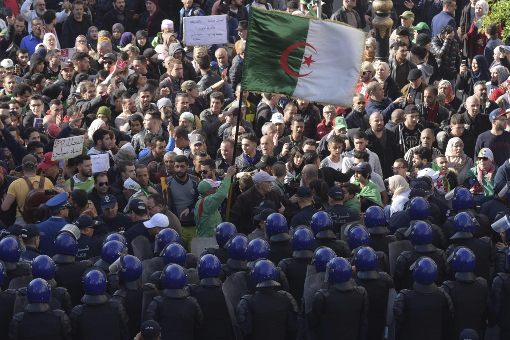 Security forces stand guard as Algerian demonstrators take to the streets in the capital Algiers to protest against the government and reject the upco...