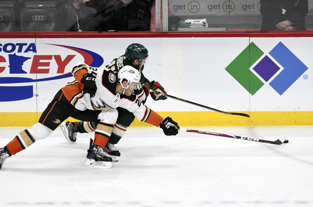 Minnesota Wild's Zach Parise, back, and Anaheim Ducks' Carter Rowney, front, go after the puck in the first period of an NHL hockey game, Tuesday, Dec...