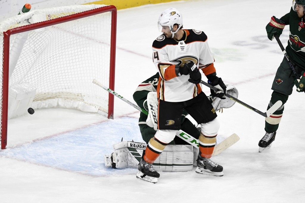 Anaheim Ducks' Adam Henrique tips the puck past Minnesota Wild goalie Kaapo Kahkonen, of Finland, for a power play goal in the first period of an NHL ...