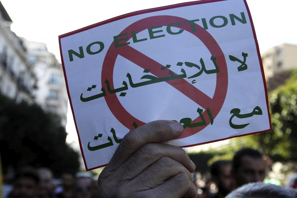 FILE - In this Dec. 6, 2019 file photo, people demonstrate with anti-election posters in Algiers. Algeria's powerful army chief promises that a presid...