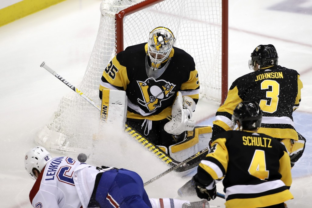 Pittsburgh Penguins goaltender Tristan Jarry (35) stops a shot by Montreal Canadiens' Artturi Lehkonen (62) with Justin Schultz (4) and Jack Johnson (...