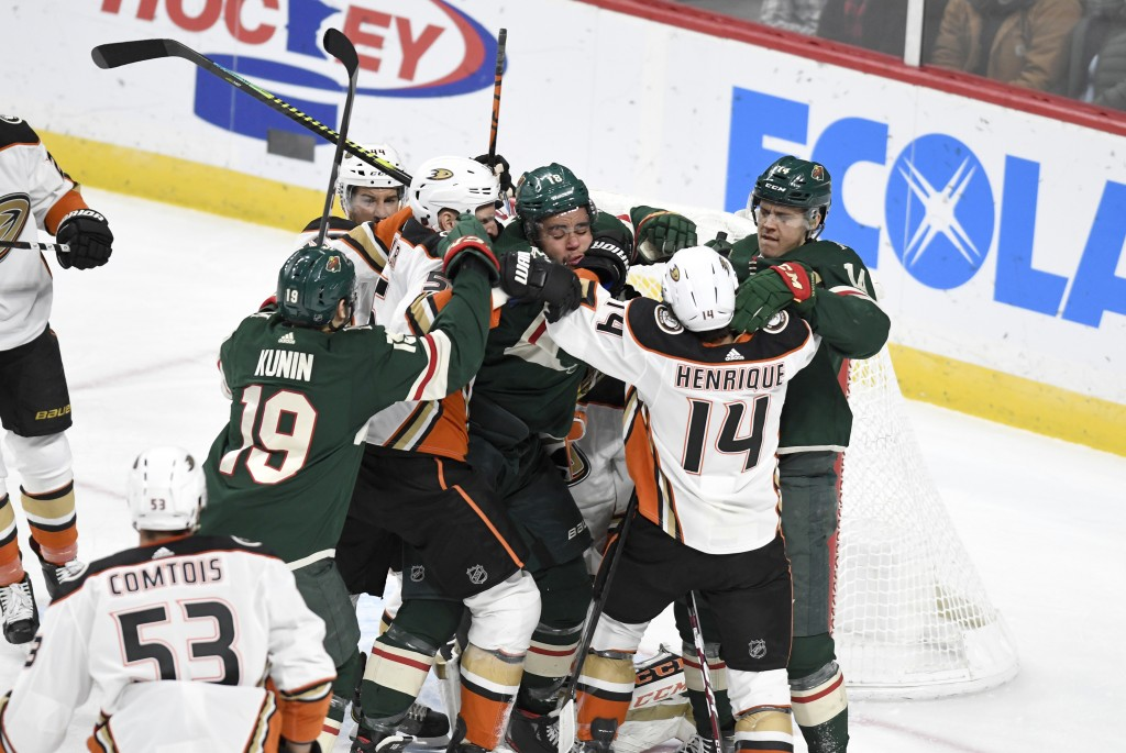 Minnesota Wild's Jordan Greenway, center, is surrounded by Wild teammates and Anaheim Duck players after getting off a shot on the Ducks' goal in the ...