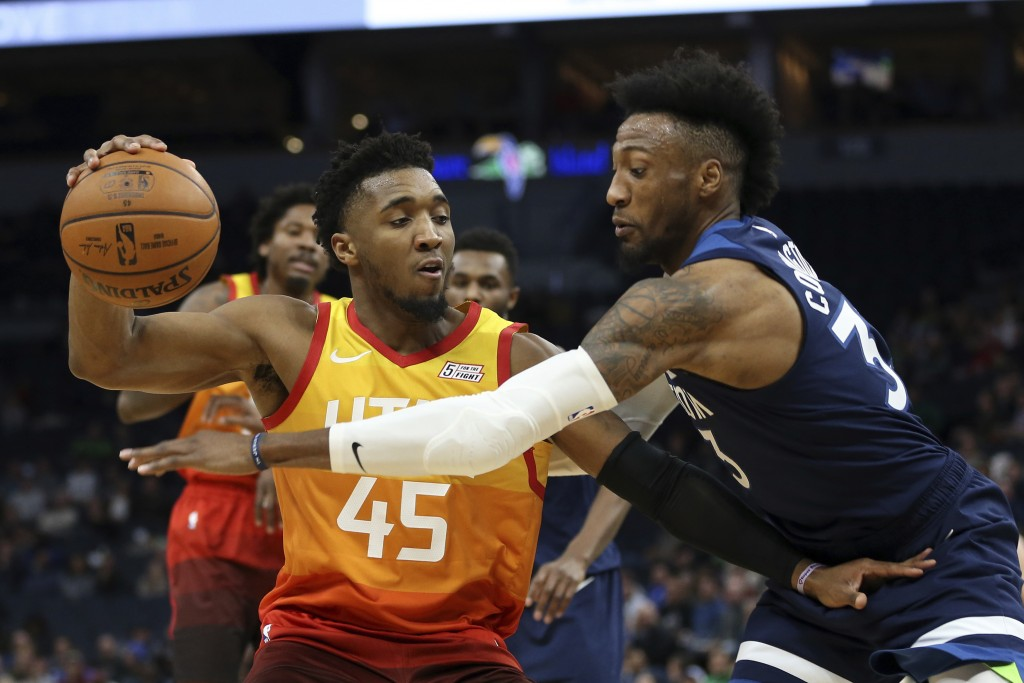 Utah Jazz's Donovan Mitchell controls the ball against Minnesota Timberwolves' Robert Covington in the first half of an NBA basketball game Wednesday,...