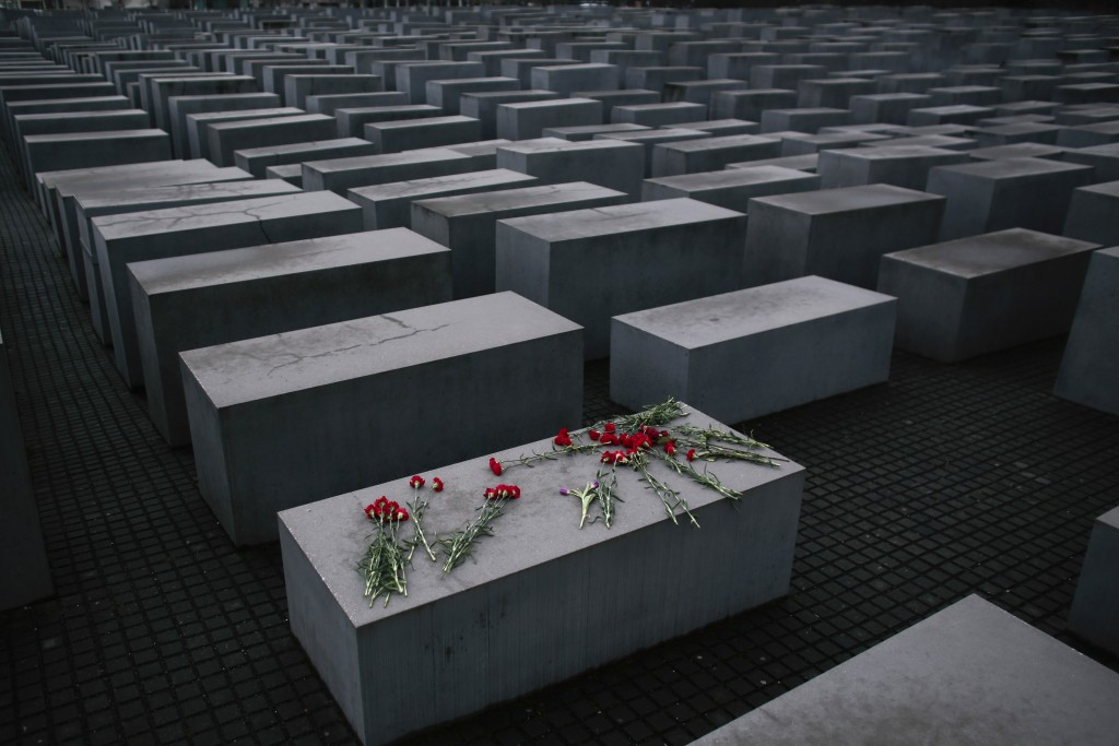 In this Tuesday, Jan. 27, 2015 file photo, flowers lay on a concrete slab of the Holocaust Memorial to mark the International Holocaust Remembrance Da...