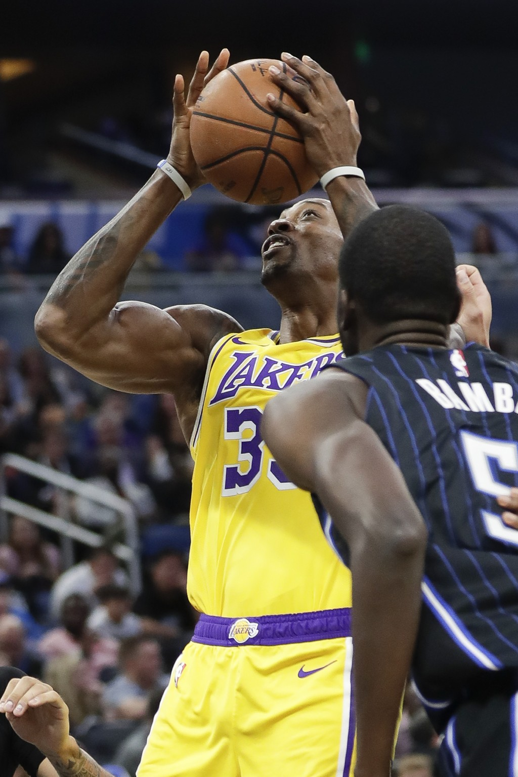 Los Angeles Lakers center Dwight Howard, left, works to get off a shot over Orlando Magic's Mo Bamba, right, during the first half of an NBA basketbal...