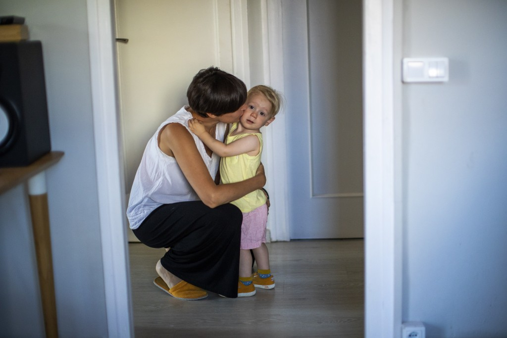 In this photo taken on Wednesday, June 19, 2019, Clara Massons kisses her two years old son Jaume at her home in Barcelona, Spain. Outdated medical pr...