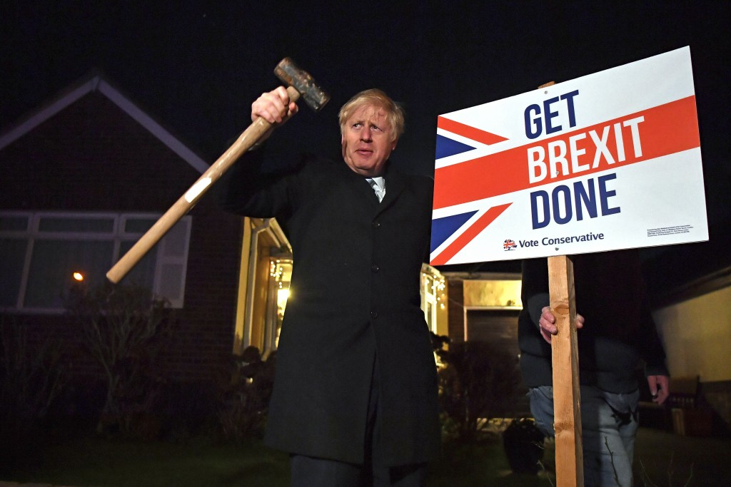 """Britain's Prime Minister and Conservative party leader Boris Johnson poses as he hammers a """"Get Brexit Done"""" sign into the garden of a supporter, in B..."""