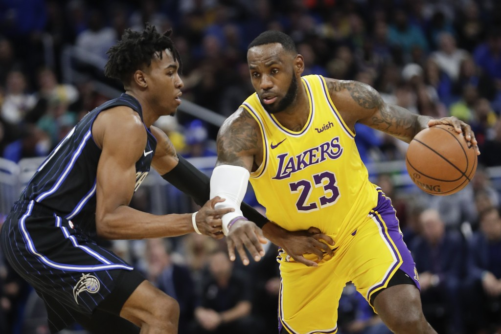 Los Angeles Lakers' LeBron James (23) drives around Orlando Magic's Wes Iwundu, left, during the first half of an NBA basketball game, Wednesday, Dec....
