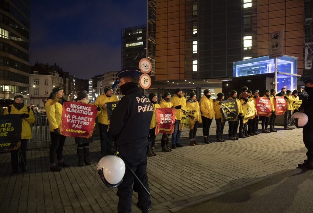 Police watch over climate activists as they demonstrate outside of an EU summit meeting in Brussels, Thursday, Dec. 12, 2019. (AP Photo/Virginia Mayo)