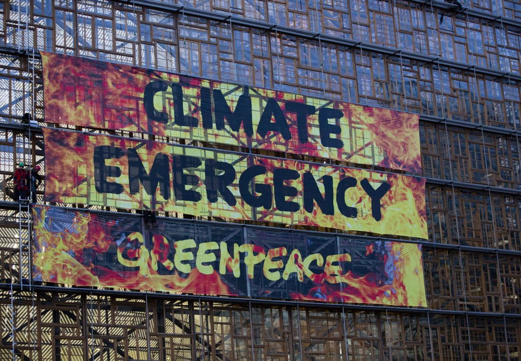 Climate activists stand in the scaffolding of the Europa building and unfurl a banner outside of an EU summit meeting in Brussels, Thursday, Dec. 12, ...