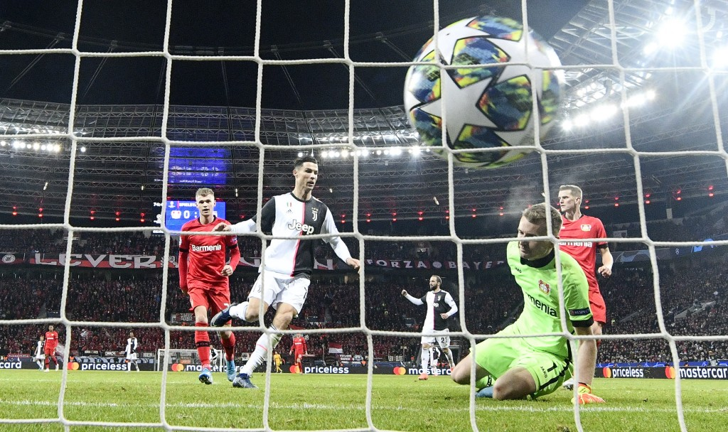 Juventus' Cristiano Ronaldo, center, scores the opening goal against Leverkusen's goalkeeper Lukas Hradecky during the Champions League Group D soccer...