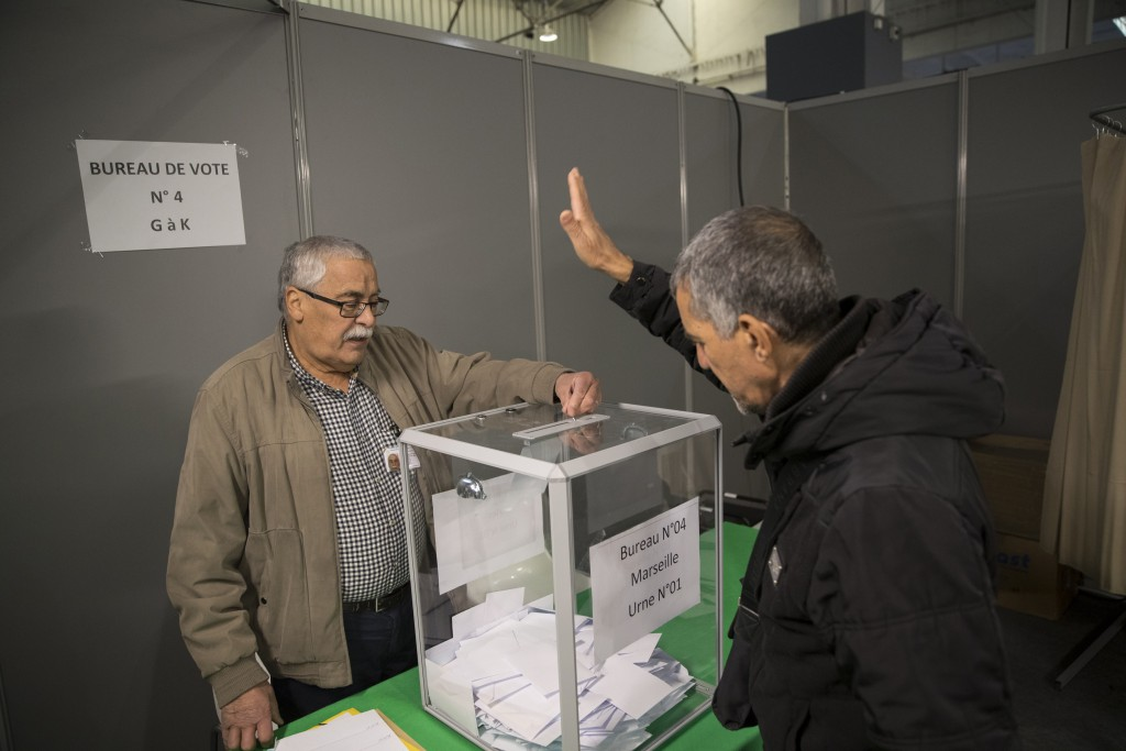 A Algerian voter casts his vote, Thursday, Dec.12, 2019, at the Algerian consulate in Marseille, southern France. Five candidates have their eyes on b...