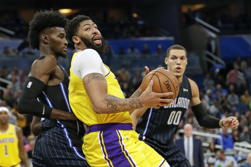 Los Angeles Lakers forward Anthony Davis, center, looks for a way to the basket around Orlando Magic forward Jonathan Isaac, left, and Aaron Gordon (0...