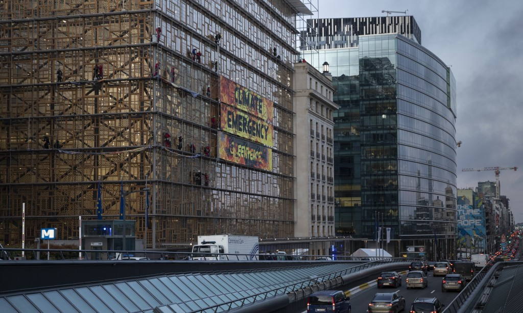 Climate activists unfurl a banner as they stand in the scaffolding of the Europa building outside of an EU summit meeting in Brussels, Thursday, Dec. ...