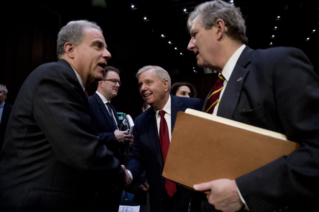 Department of Justice Inspector General Michael Horowitz, left, speaks with Chairman Lindsey Graham, R-S.C., center, and Sen. John Kennedy, R-La., rig...