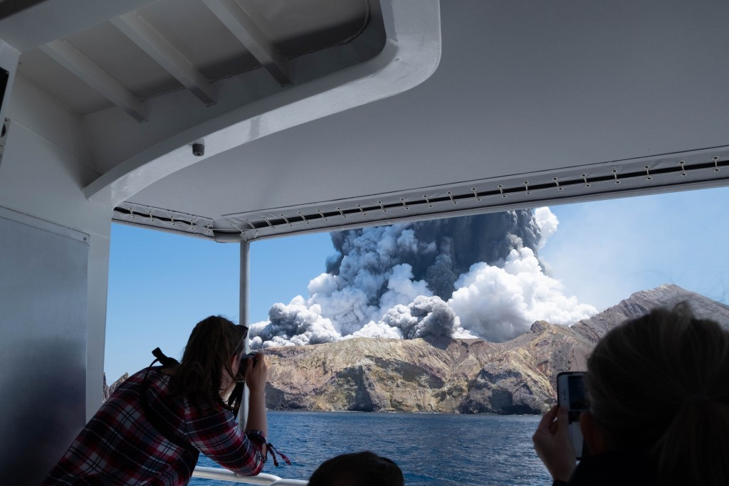 In this Dec. 9, 2019, file photo provided by Michael Schade, tourists on a boat look at the eruption of the volcano on White Island, New Zealand. Unst...