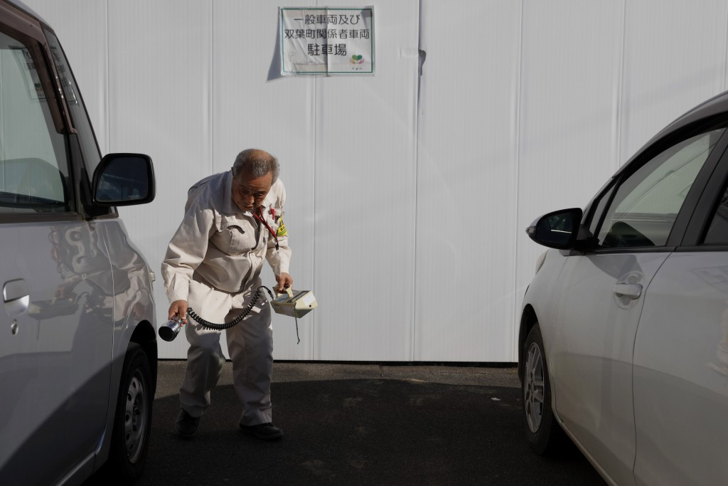 A worker checks the radiation level in the parking lot of a construction company Tuesday, Dec. 3, 2019, in Futaba, Fukushima prefecture, Japan. Most o...