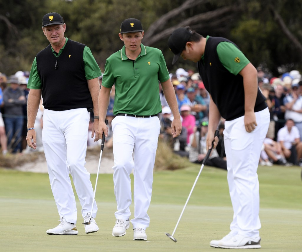 International team captain Ernie Els, left, looks over the 18th green with players Cameron Smith of Australia and Sung Jae Im of South Korea, right, i...