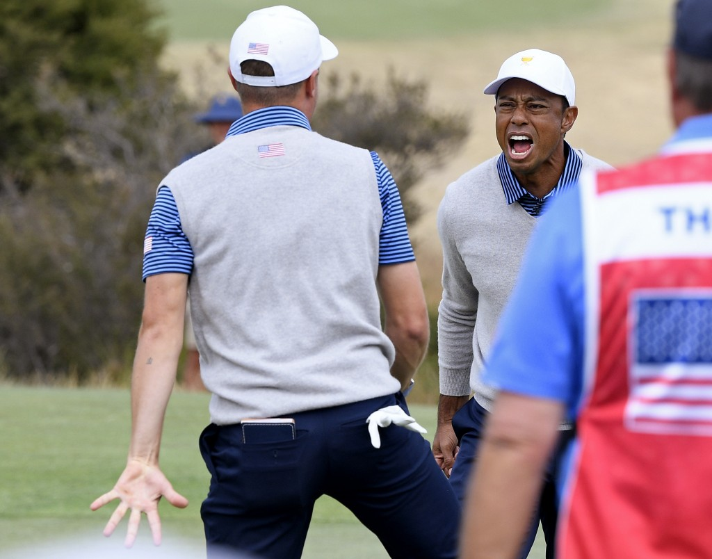 U.S. team player Justin Thomas, left, celebrates with his playing partner and captain, Tiger Woods, on the 18th green in their foursomes match during ...