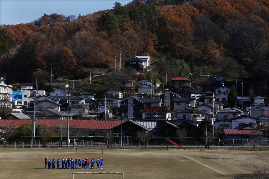 Elementary school children gather on the school ground Friday, Nov. 29, 2019, in Kawamata, Fukushima prefecture, Japan. Some schools in the area are c...