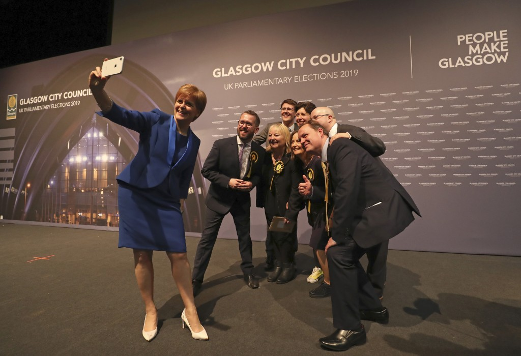 Scottish First Minister Nicola Sturgeon takes a photo with party members at the SEC Centre in Glasgow after the declaration in her constituency in the...