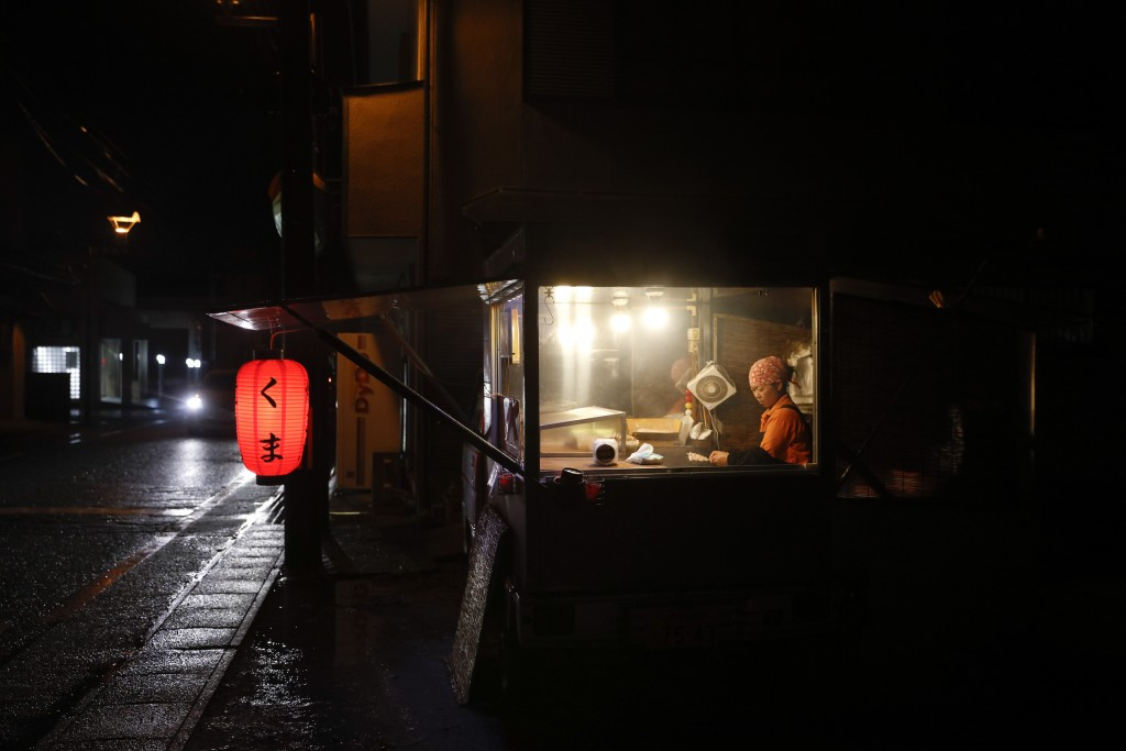 Yakitory cook Akemi Kumagai works in her shack Wednesday, Nov. 27, 2019, in Hirono, Fukushima prefecture, Japan. The costal area of the town was devas...