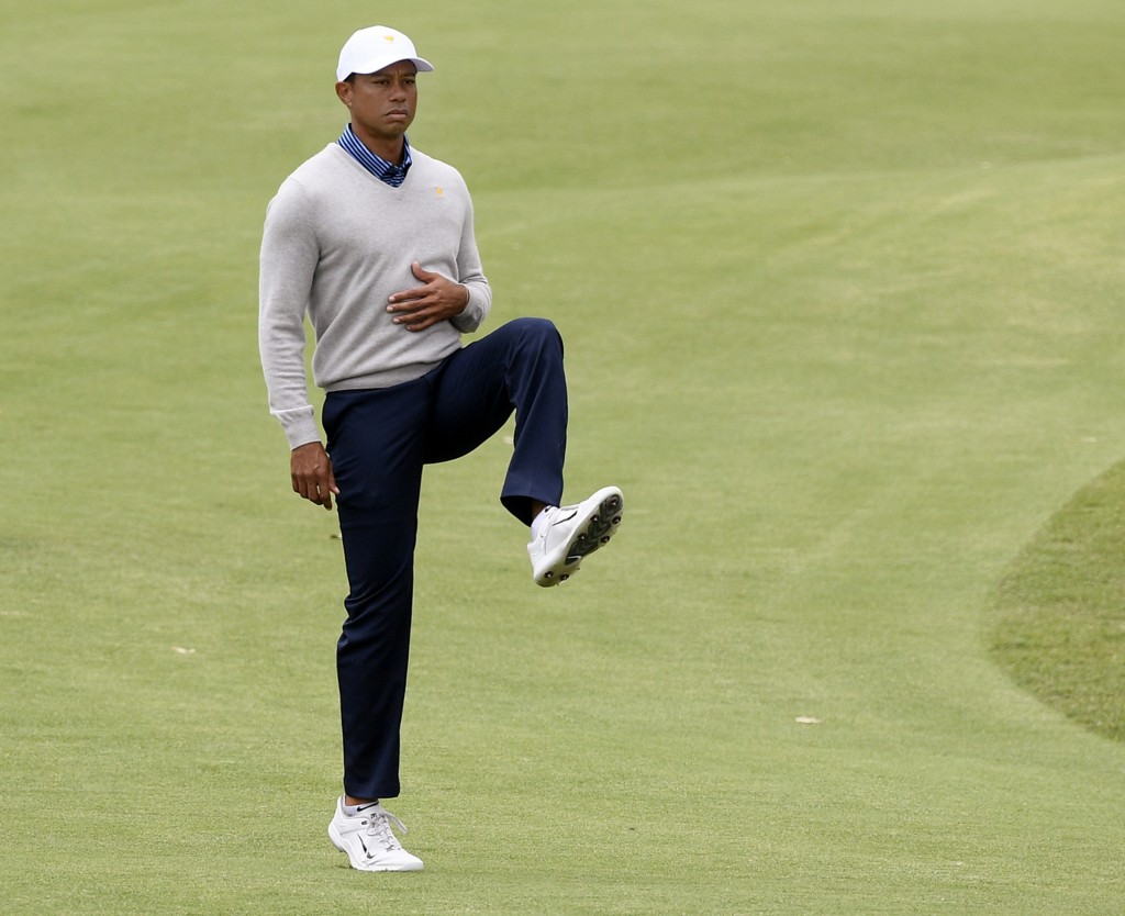 U.S. team player and captain Tiger Woods stretches his leg on the 7th fairway in their foursomes match during the President's Cup golf tournament at R...