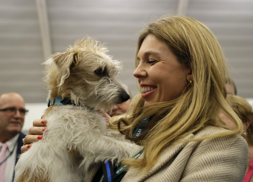 Carrie Symonds, the partner of Britain's Prime Minister and Conservative Party leader Boris Johnson holds their dog Dilyn after arriving for the Uxbri...