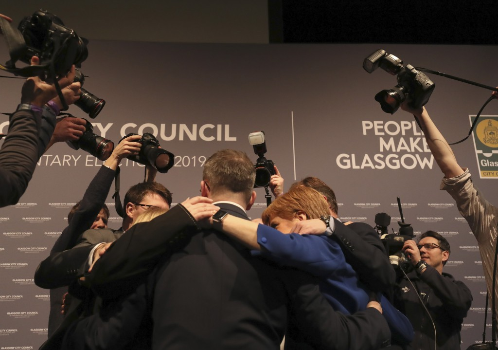 Scottish First Minister Nicola Sturgeon forms a huddle with party members at the SEC Centre in Glasgow after the declaration in her constituency in th...