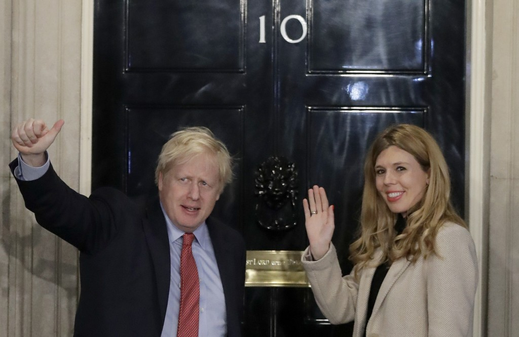 Britain's Prime Minister Boris Johnson and his partner Carrie Symonds wave from the steps of number 10 Downing Street in London, Friday, Dec. 13, 2019...