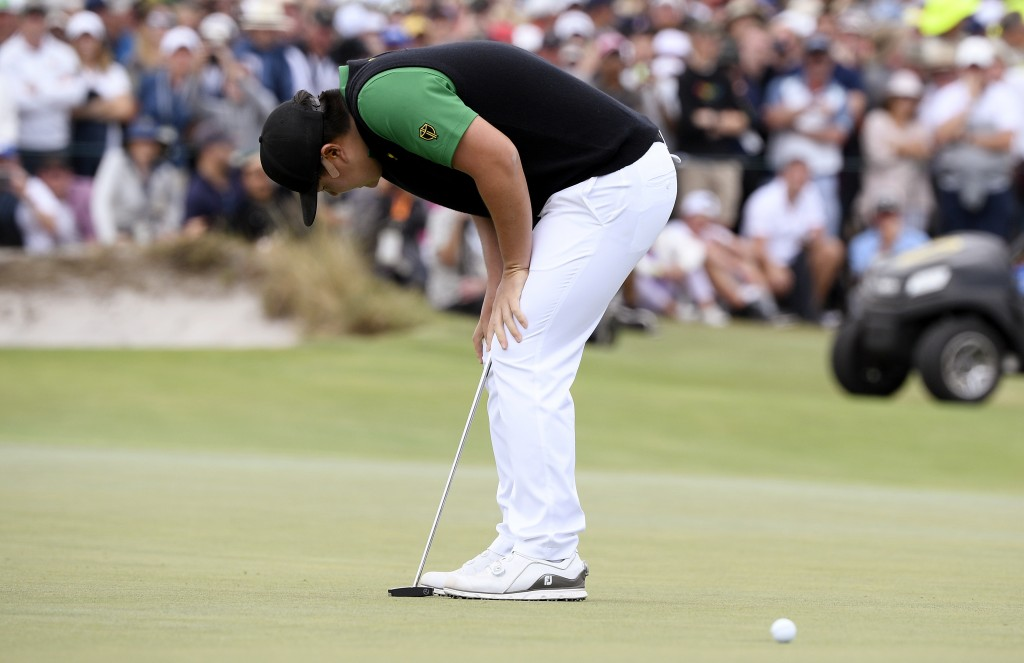 International team player Sung Jae Im of South Korea, bends over after missing a putt on the 18th green in their foursomes match during the President'...