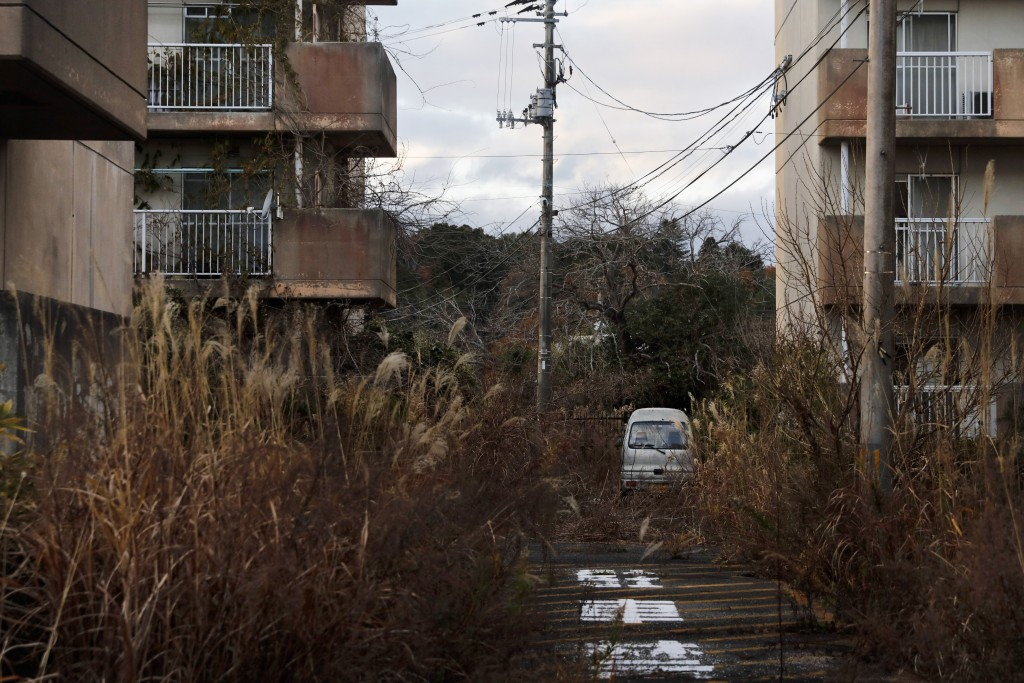"""Weeds grow in an abandoned apartment complex Tuesday, Dec. 3, 2019, in Futaba, Fukushima prefecture, Japan. Government officials say it's """"recovery Ol..."""