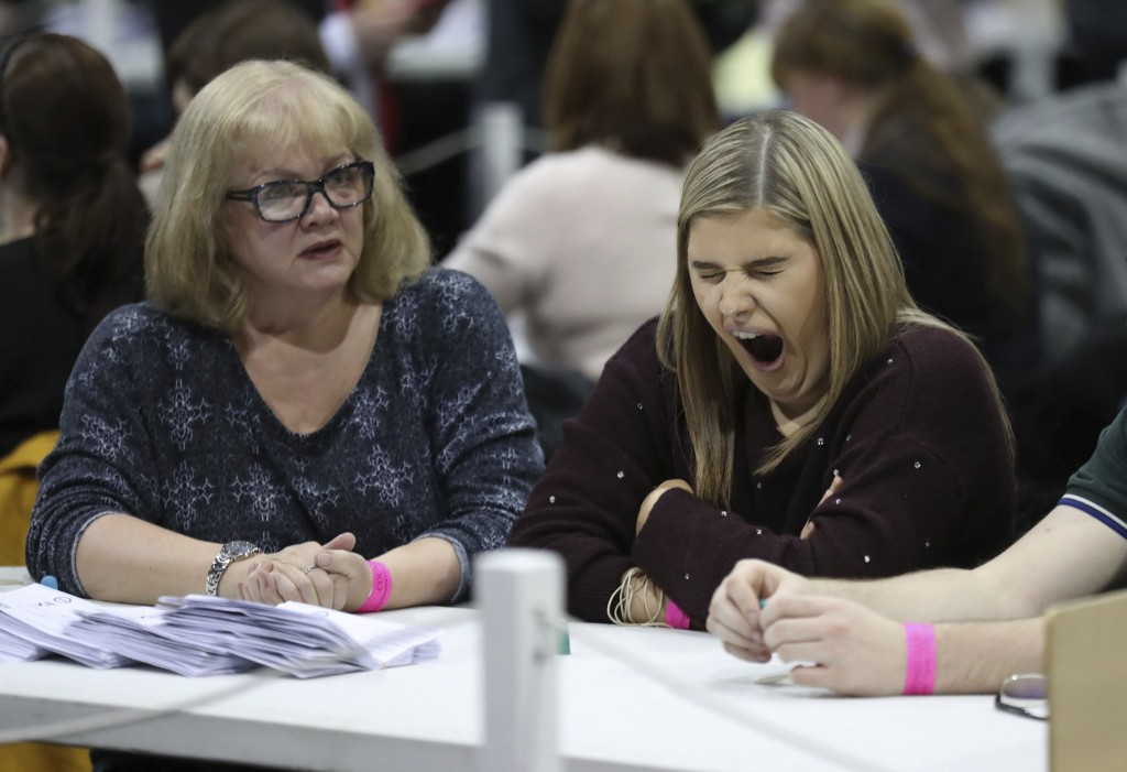 A member of the counting staff yawns as ballot papers are counted at the SEC Centre in Glasgow, Scotland Friday Dec. 13, 2019. An exit poll in Britain...
