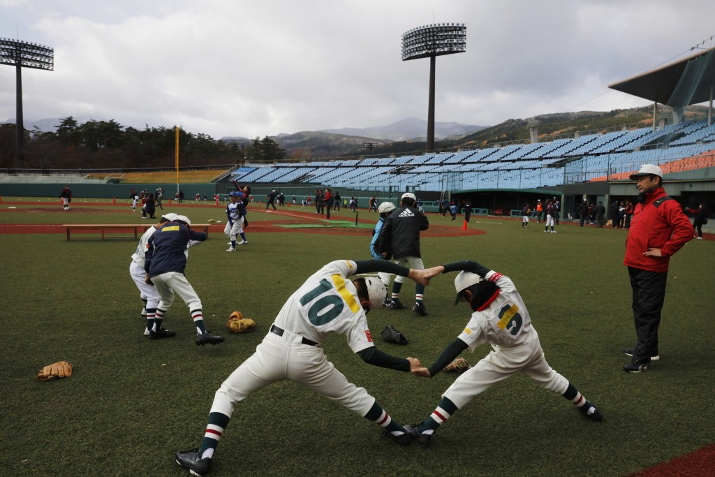 CORRECTS SPELLING TO AZUMA INSTEAD OF AZUMI - Young baseball players stretch during a festival held to celebrate the city's hosting of baseball and so...