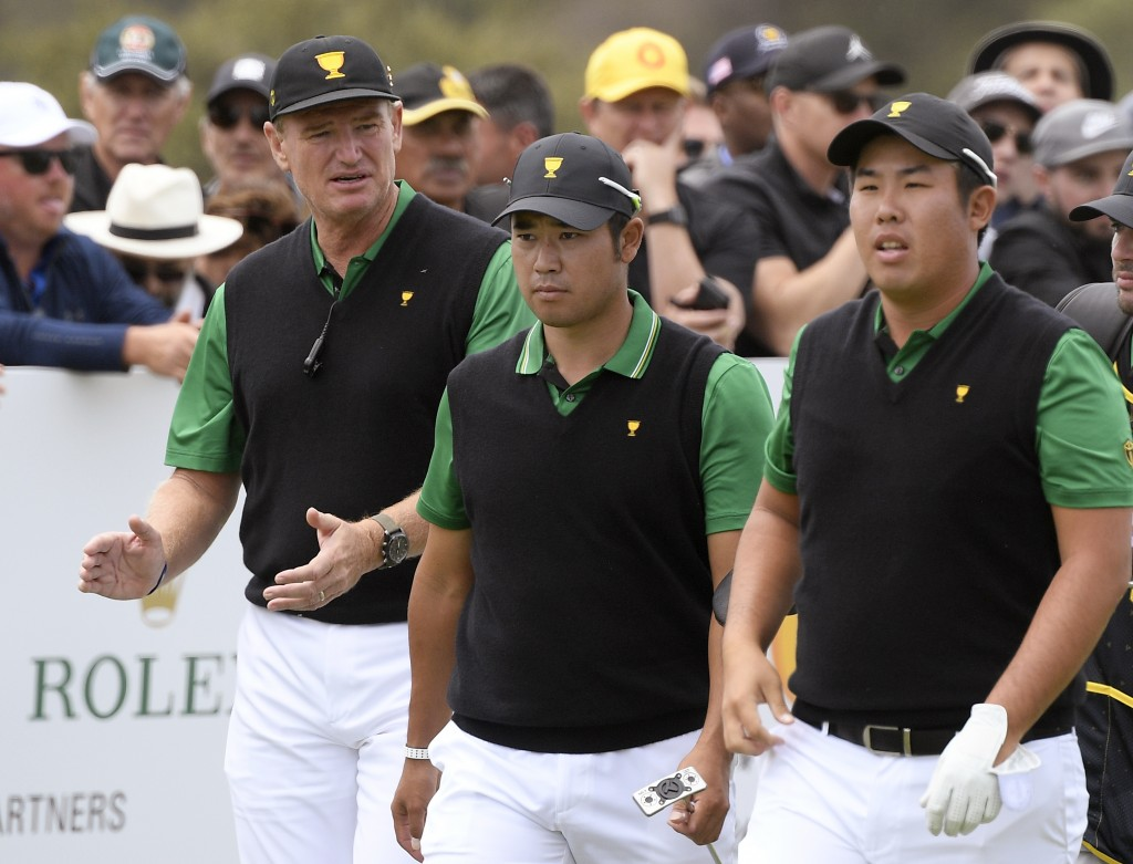 International team captain Ernie Els, left, Hideki Matsuyama of Japan and Byeong Hun An of South Korea, right, walk off the 5th tee in their foursomes...
