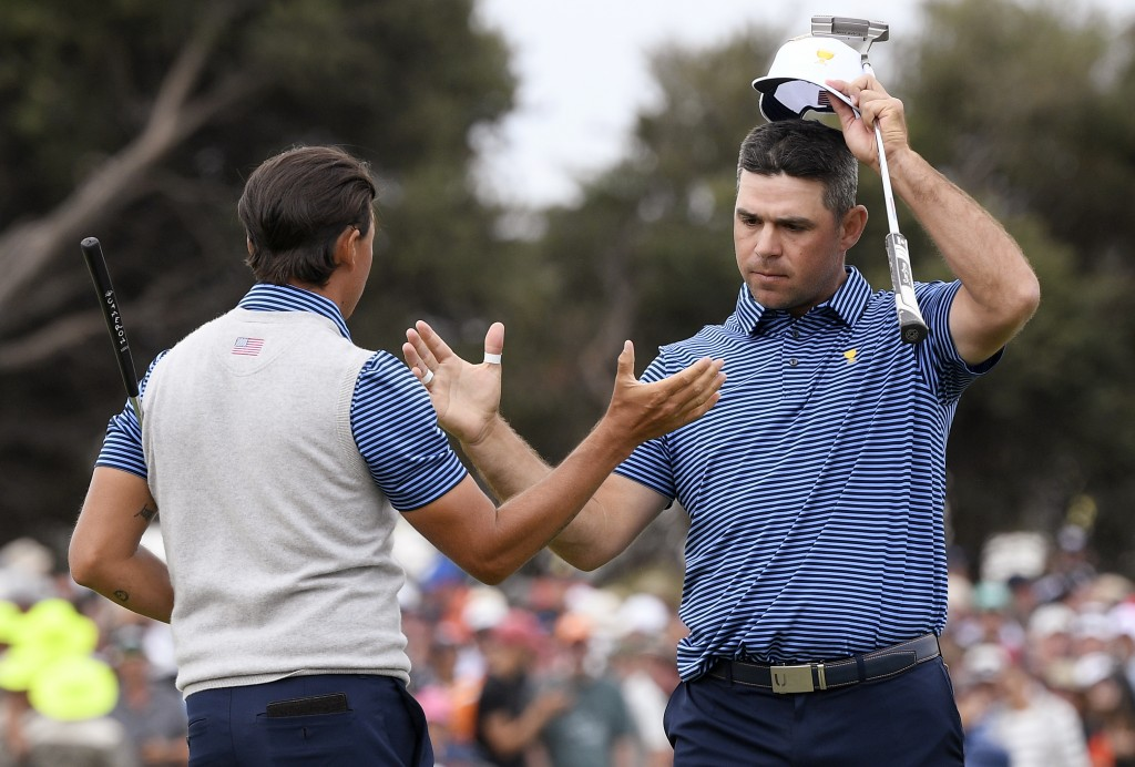 U.S. team player Rickie Fowler, left, and playing partner Gary Woodland shake hands after their foursomes match during the President's Cup golf tourna...