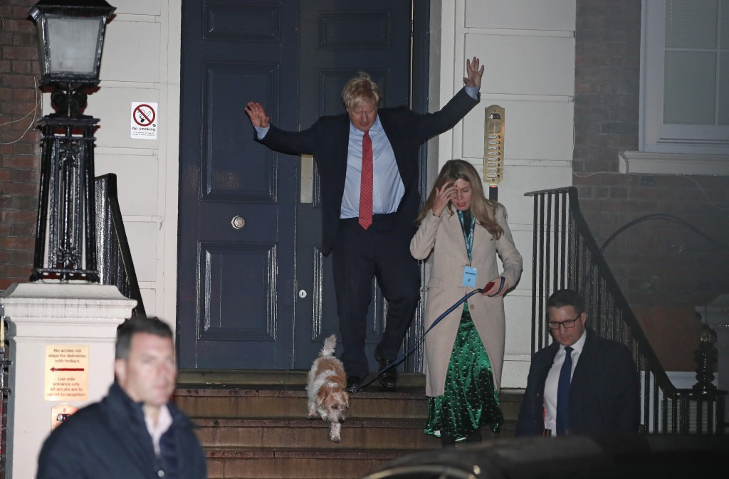 Britain's Prime Minister and Conservative Party leader Boris Johnson leaves Conservative Party headquarters with his partner Carrie Symonds and their ...