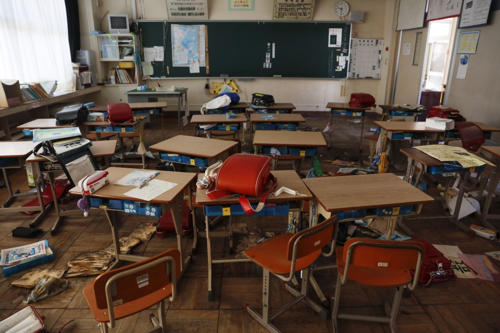 An abandoned elementary school classroom is cluttered with school bags and other belongings left by students as they rushed out after the March 2011 e...